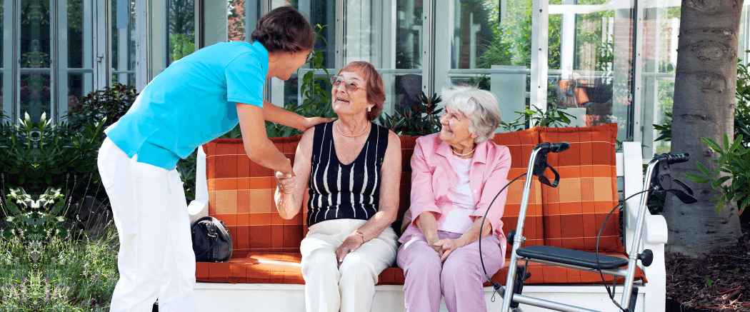 two elderly woman and a caregiver