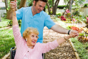 caregiver assisting an elder woman in exercising