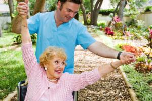 caregiver assisting an elder woman in exercising