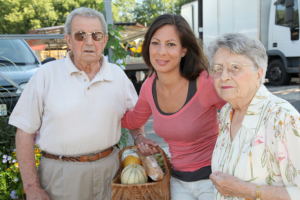 woman assisting two elderly seniors in buying groceries